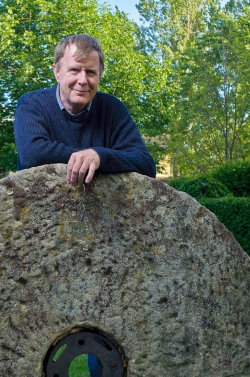 Dave Burnett with millstone in front of Miller Barn, Fanshawe Pioneer Village (Photo credit: Michael Gelman)